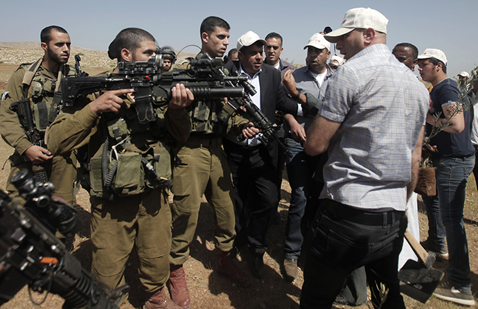 Palestinian men (right) who were trying to plant olives trees on land close to an Israeli military camp in the Jordan Valley, argue with Israeli soldiers after they were asked to leave the area, on April 8, 2014 in the occupied West Bank. (AFP Photo / Jaafar Ashtiyeh)