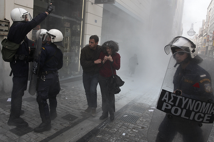 People walk from tear gas during scuffles between police and protesters demonstrating against the government's decision to allow shops to open for more than two Sundays a year, in the commercial Ermou Street in central Athens April 13, 2014. (Reuters / Alkis Konstantinidis)