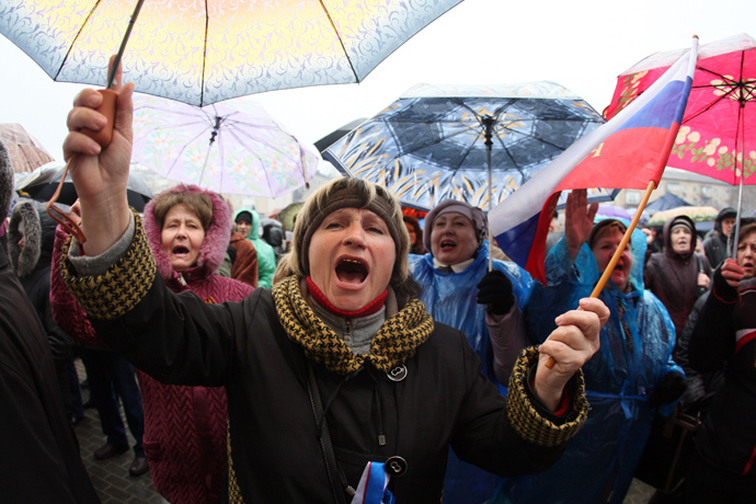Pro-Russian activists hold umbrellas under the rain and shout slogans during a rally near a barricade outside the regional government building in the eastern Ukrainian city of Donetsk on April 13, 2014 (AFP Photo / Alexander Khudoteply)