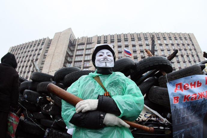 A pro-Russian activist wearing a Guy Fawkes mask and holding a bat guards a barricade outside the regional government building in the eastern Ukrainian city of Donetsk on April 13, 2014 (AFP Photo / Alexander Khudoteply)