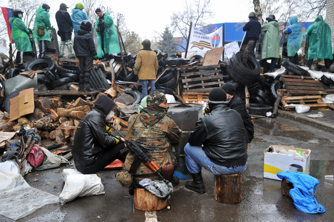 Pro-Russia activists warm themselves near a barricade outside a regional police building seized by armed separatists in Slavyansk on April 13, 2014 (AFP Photo / Genya Savilov)