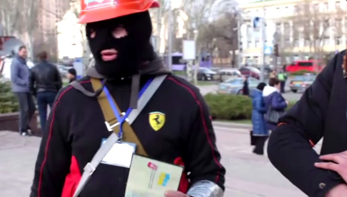 A protester in Donetsk shows his Ukrainian passport. Still from RT video