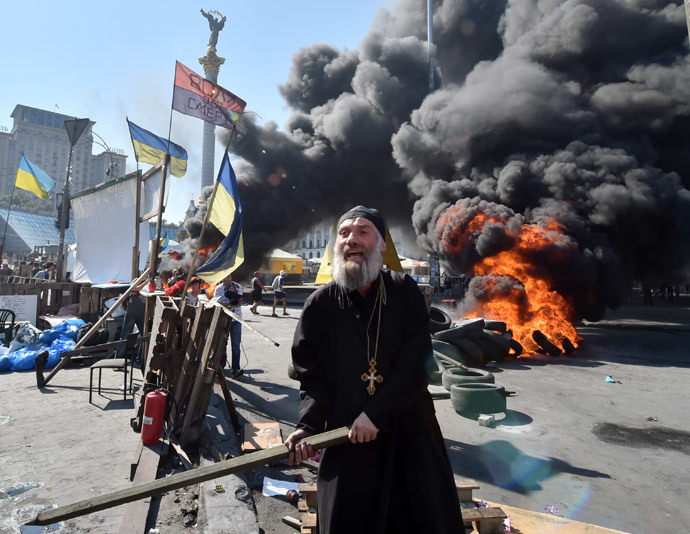An Orthodox priest gestures with a stick and shouts as Maidan self-defence activists clash with fighters of Kiev-1 volunteer battalion on Independence Square in Kiev on August 7, 2014.(AFP Photo / Sergei Supinsky)