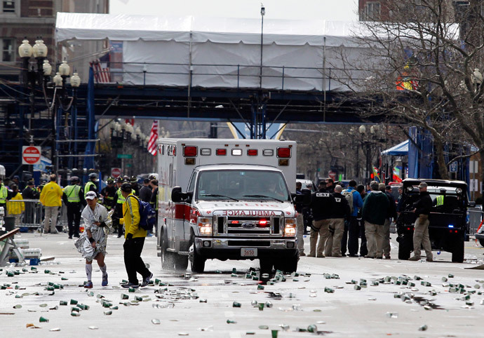A runner is escorted from the scene after explosions went off at the 117th Boston Marathon in Boston, Massachusetts April 15, 2013. (Reuters / Jessica Rinaldi)