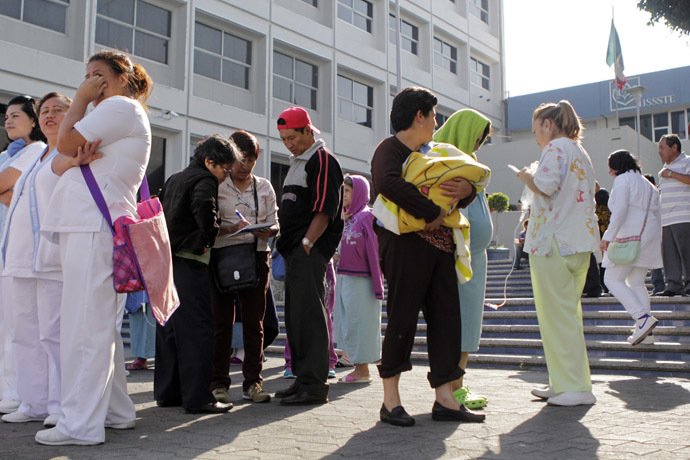 People stand along a street after evacuating a hospital following an earthquake in Puebla April 18, 2014. (Reuters/Imelda Medina)