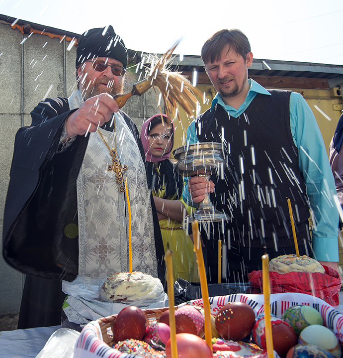 A Russian Orthodox priest blesses cakes and colored eggs during an Orthodox Easter ceremony in Moscow, on April 19, 2014, on the eve of the Orthodox Easter. (AFP Photo / Anatoly Tanin)