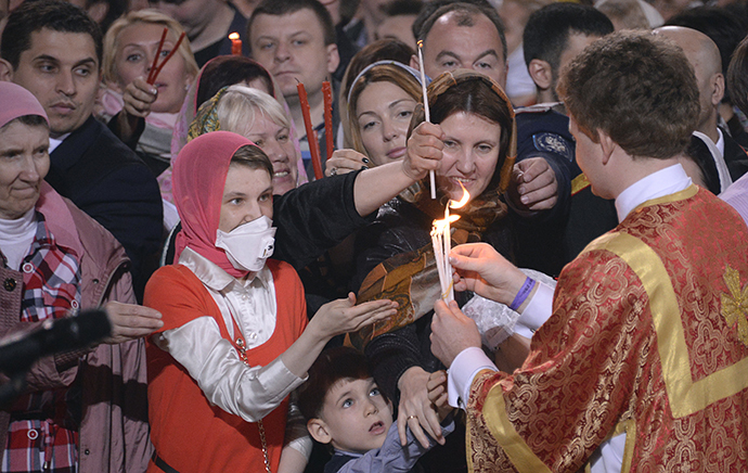 Believers receive the Holly Light during an Orthodox Easter service in Moscow, early on April 20, 2014. (AFP Photo / Alexander Nemenov)