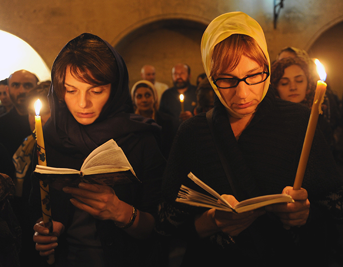 Georgian Orthodox believers attend a service as they celebrate an Orthodox Easter in a church in Tbilisi early on April 20, 2014. (AFP Photo / Vano Shlamov)