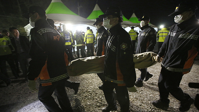South Korean rescue workers carry the body of a passenger onboard the capsized passenger ship Sewol, at a port where family members of missing passengers are gathered, in Jindo April 19, 2014. (Reuters / Issei Kato)
