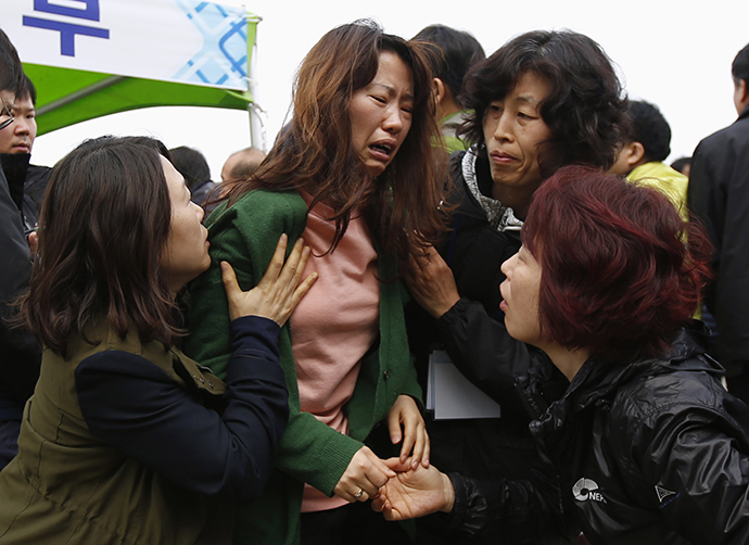 A family member of missing passengers (C) who were on the South Korean ferry Sewol which sank in the sea off Jindo, cries as she found the name of her family in the list of fatalities at a port where family members of missing passengers gathered, in Jindo April 20, 2014. (Reuters / Issei Kato)