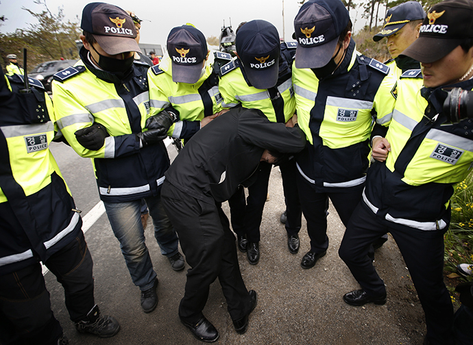 """A family member of a passenger missing after the South Korean ferry """"Sewol"""" capsized is blocked by police during a protest in Jindo calling for a meeting with President Park Geun-hye and demanding the search and rescue operation be speeded up, April 20, 2014. (Reuters / Kim Kyung Hoon)"""