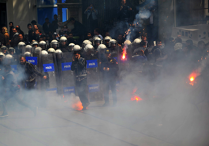 Fenerbahce and Besiktas throw flares at the police as they protest against a new system of e-tickets on April 20, 2014, on Istiklal Avenue in Istanbul. (AFP Photo / Ozan Kose)