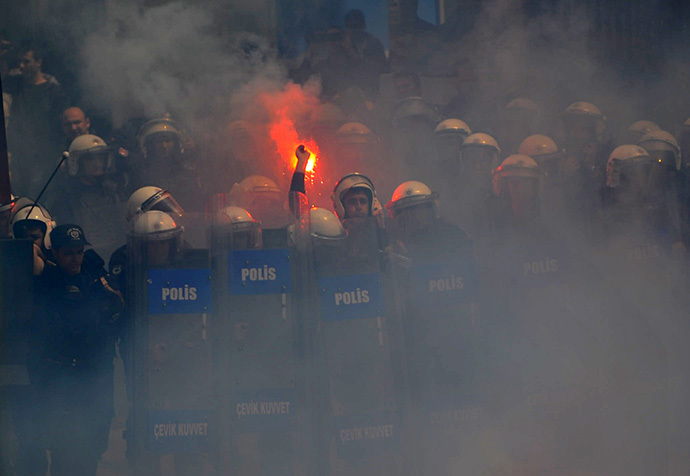 A Turkish police throws a flare back to football fans as they protest against a new system of e-tickets on April 20, 2014, on Istiklal Avenue in Istanbul. (AFP Photo / Ozan Kose)