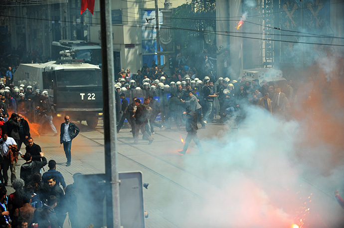 Galatasaray, Fenerbahce and Besiktas throw flares at the police as they protest against a new system of e-tickets on April 20, 2014, on Istiklal Avenue in Istanbul. (AFP Photo / Ozan Kose)