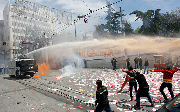 Soccer fans throw flares at riot police, who use a water cannon against them, during a protest against the new e-ticket system in Istanbul April 20, 2014. (Reuters / Murad Sezer)