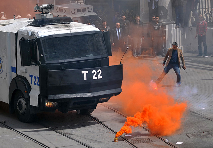 A smoke flare is seen in front of a police vehicle as Galatasaray, Fenerbahce and Besiktas clashed with riot police during a protest against a new system of e-tickets on April 20, 2014, on Istiklal Avenue in Istanbul. (AFP Photo / Ozan Kose)