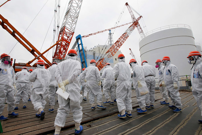 Members of the media and Tokyo Electric Power Co. (TEPCO) employees wearing protective suits and masks walk toward the No. 1 reactor building at the tsunami-crippled TEPCO's Fukushima Daiichi nuclear power plant in Fukushima prefecture March 10, 2014.(Reuters / Toru Hanai)