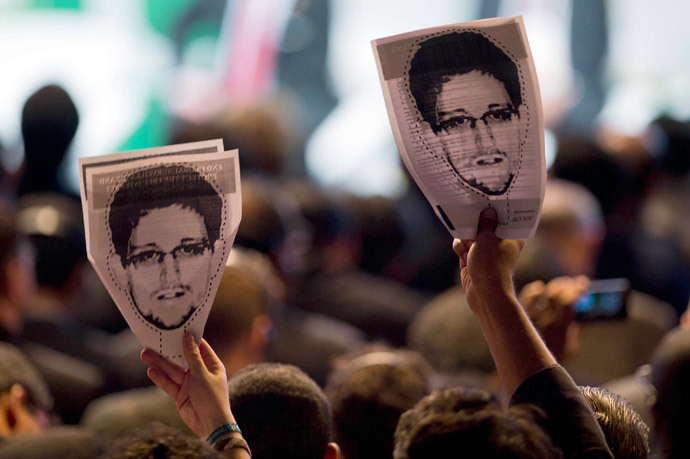 "Demonstrators holding papers to be cut to make portraits of Edward Snowden protest during the opening ceremony during the opening ceremony of the ""NETmundial – Global Multistakeholder Meeting on the Future of Internet Governance"", on April 23, 2014 in Sao Paulo, Brazil.(AFP Photo / Nelson Almeida)"