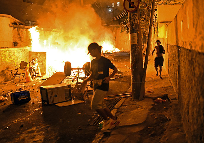Residents run for cover during violent clashes between protestors and Brazilian Police Special Forces in a favela near Copacabana in Rio de Janeiro, Brazil on April 22, 2014. (AFP Photo / Christophe Simon)