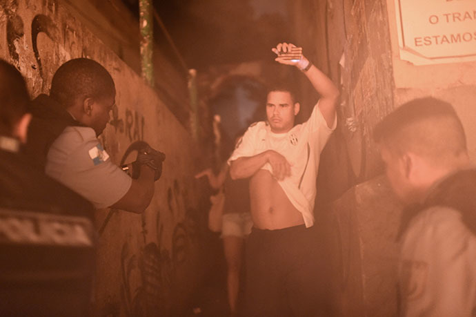 Brazilian Police Special Force members detain a man during a violent protest in a favela near Copacabana in Rio de Janeiro, Brazil on April 22, 2014. (AFP Photo / Christophe Simon)