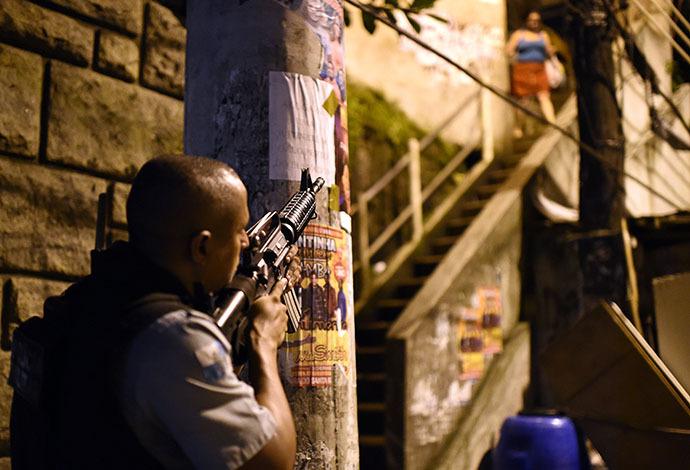 A Brazilian Police Special Forces member takes position during a violent protest in a favela near Copacabana in Rio de Janeiro, Brazil on April 22, 2014. (AFP Photo / Christophe Simon)