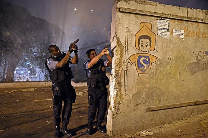 Rio de Janeiro's state military policemen aim their guns during a violent protest in a favela next to Copacabana, Rio de Janeiro on April 22, 2014. (AFP Photo / Christophe Simon)