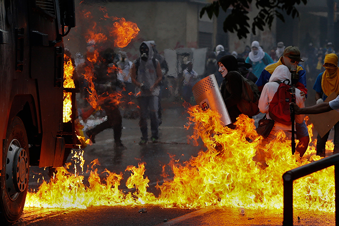 An anti-government protester, wearing a Guy Fawkes mask, stands with a shield near flames from molotov cocktails thrown at a water cannon by anti-government protesters during riots in Caracas April 20, 2014 (Reuters / Jorge Silva)