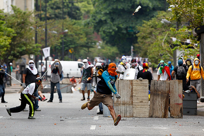 An anti-government protester throws a Molotov cocktail during riots with police in Caracas April 17, 2014 (Reuters / Christian Veron)