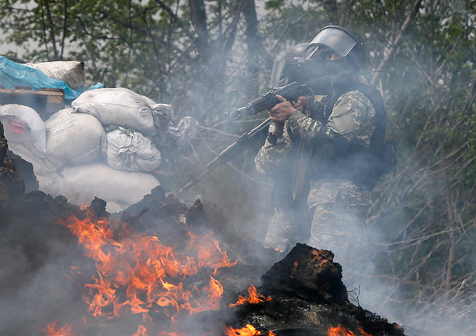 Ukrainian security force officers walk past a checkpoint set on fire and left by anti-goverment protesters near Slavyansk April 24, 2014 (AFP Photo / Gleb Garanich)