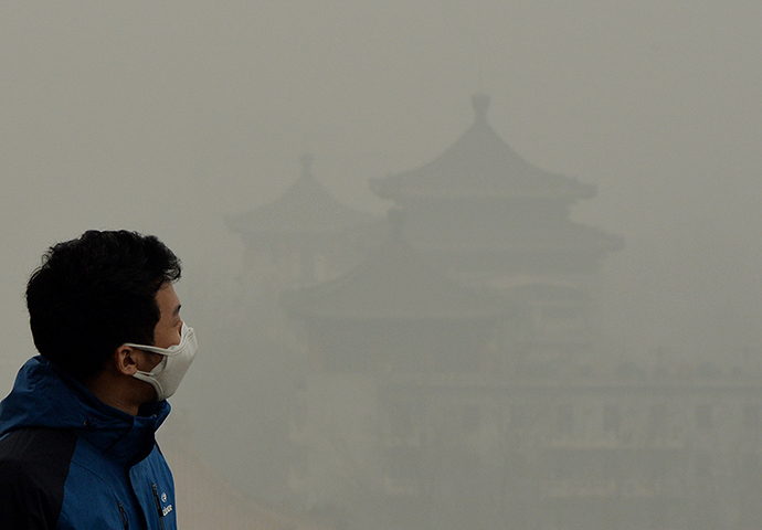 A tourist wearing a face mask climbs Jingshan Hill beside the Forbidden City as heavy air pollution continues to shroud Beijing (AFP Photo / Mark Ralston)