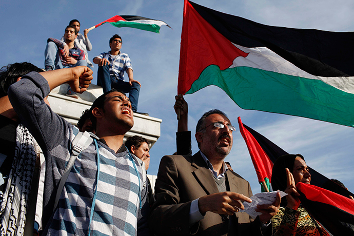 Palestinians wave national flags as they celebrate after an announcement of a reconciliation agreement in Gaza City April 23, 2014 (Reuters / Ibraheem Abu Mustafa)