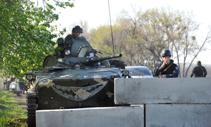 Ukrainian policeman and soldiers in a tank stand guard at their newly erected checkpoint near the eastern Ukrainain city of Slavyansk on April 25, 2014. (AFP Photo/Genya Savilov)