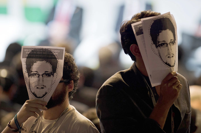 "Demonstrators hold papers to be cut to make portraits of Edward Snowden in front of their own faces ai a protest during the opening ceremony during the opening ceremony of the ""NETmundial – Global Multistakeholder Meeting on the Future of Internet Governance"", on April 23, 2014 in Sao Paulo, Brazil. (AFP Photo/Nelson Almeida)"