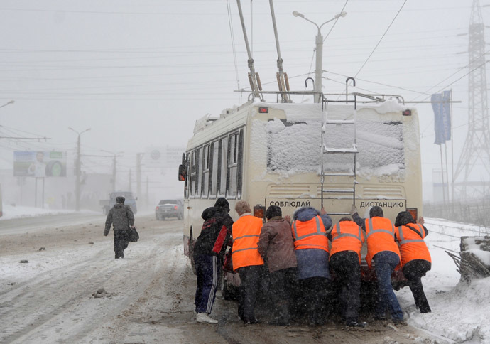 Municipal workers push a trolleybus during a heavy blizzard in Chelyabinsk, Russia (RIA Novosti/Aleksandr Kondratuk)