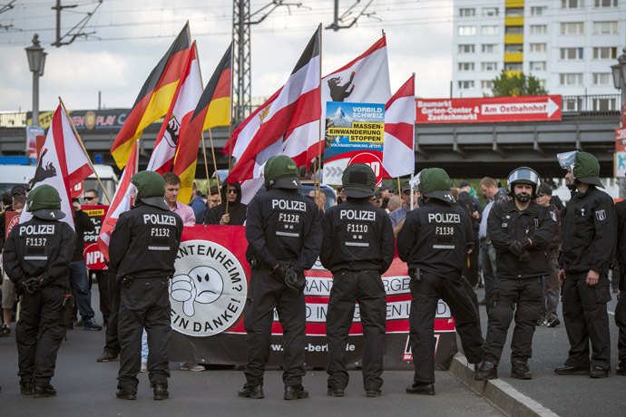 Activists from the far right party NPD are seen behind a police line at the start of their marches on the Jannowitz bridge in Berlin on April 26, 2014. (AFP Photo/Odd Andersen)