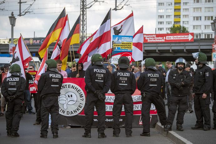 Gli attivisti del partito di estrema destra NPD sono visti dietro una linea di polizia all'inizio delle loro marce sul ponte Jannowitz a Berlino il 26 aprile 2014. (AFP Photo / Odd Andersen)