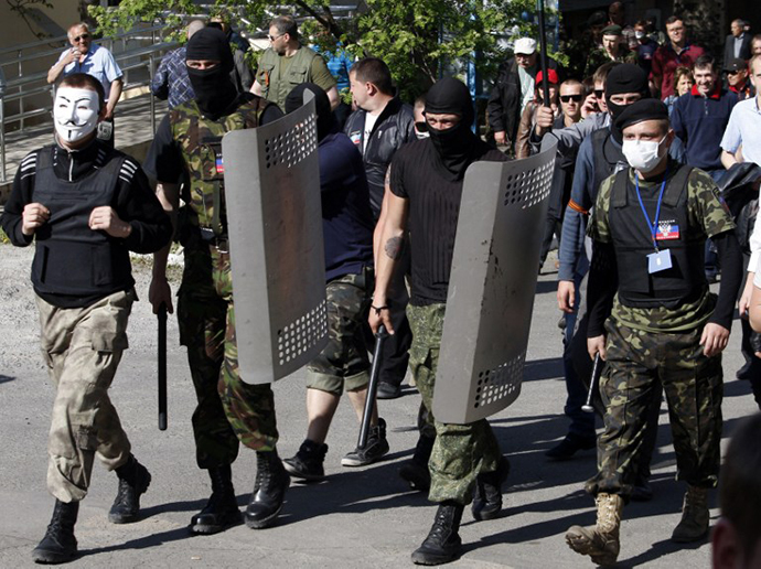 Masked activists march to seize a regional television station in the eastern Ukrainian city of Donetsk, home of the local telecommunication antennas and studios of the regional TV station Channel 27, on April 27, 2014. (AFP Photo / Anatoliy Stepanov)