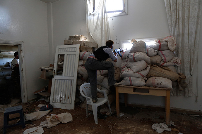 An armed rebel fighter positions himself behind sandbags in Mork town, northern Hama countryside April 26, 2014. (Reuters / Badi Khlif)