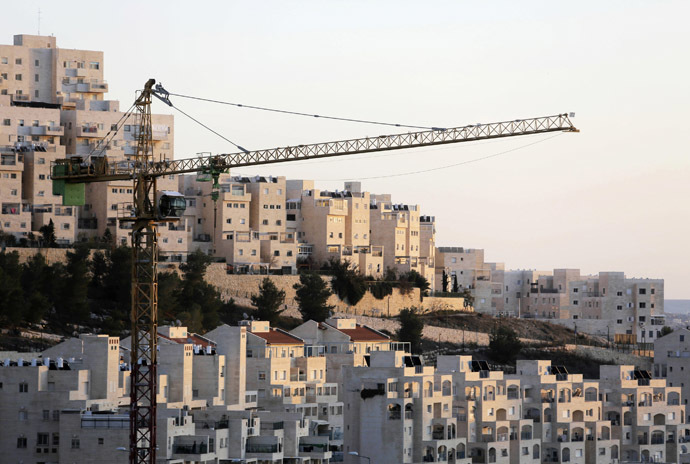 A crane is seen next to homes in a Jewish settlement near Jerusalem known to Israelis as Har Homa and to Palestinians as Jabal Abu Ghneim (Reuters)