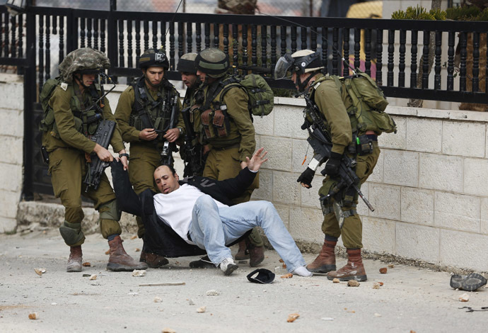 Israeli soldiers drag a Palestinian as they detain him during clashes with stone-throwing Palestinian protesters at a weekly demonstration against the West Bank Jewish settlement of Beit El, in Jalazoun refugee camp, near Ramallah (Reuters)