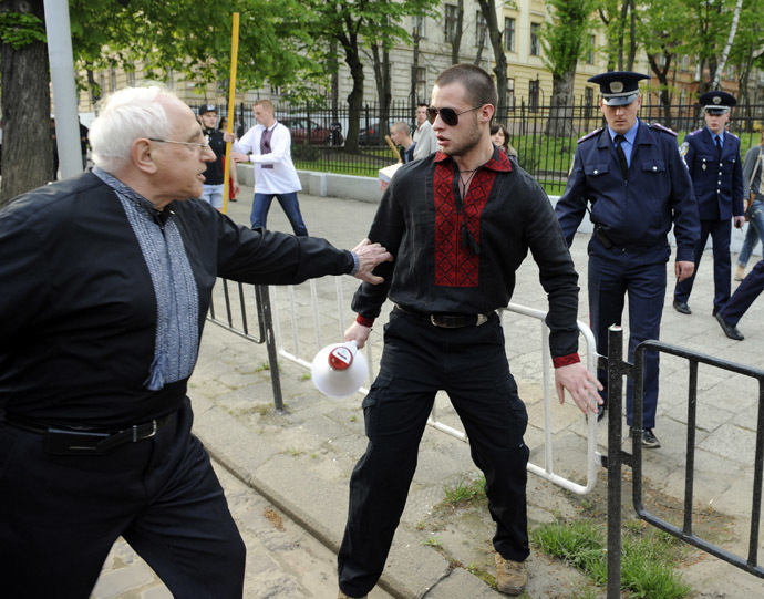 "An man (L) argues with an ultra-nationalist march participant (C) during a rally in the center of the western city of Lviv on April 27, 2014 to mark the 71st anniversary of 14th SS-Volunteer Division ""Galician"" foundation. (AFP Photo/Yuriy Dyachyshyn)"