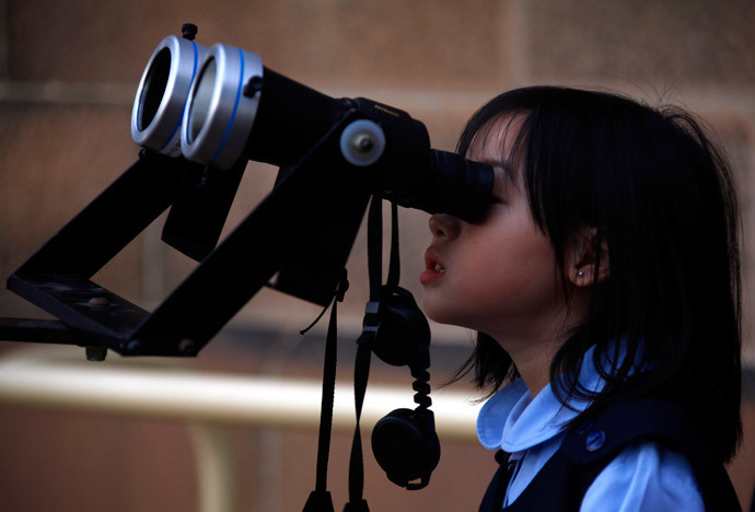 A girl looks through a telescope to try and see a partial solar eclipse from Sydney's Observatory Hill April 29, 2014. (Reuters / David Gray)