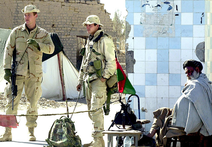 Two US Marine personnel stand alert while an Afghan soldier sits besides them on the main gate of Kandahar airport 22 January 2002. (AFP Photo / Banaras Khan)