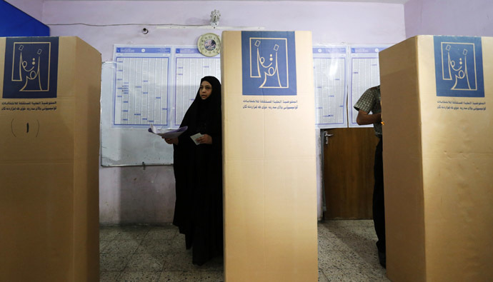 Resident mark their ballots at voting booths at a polling station during parliamentary election in Baghdad April 30, 2014. (Reuters/Thaier Al-Sudani)