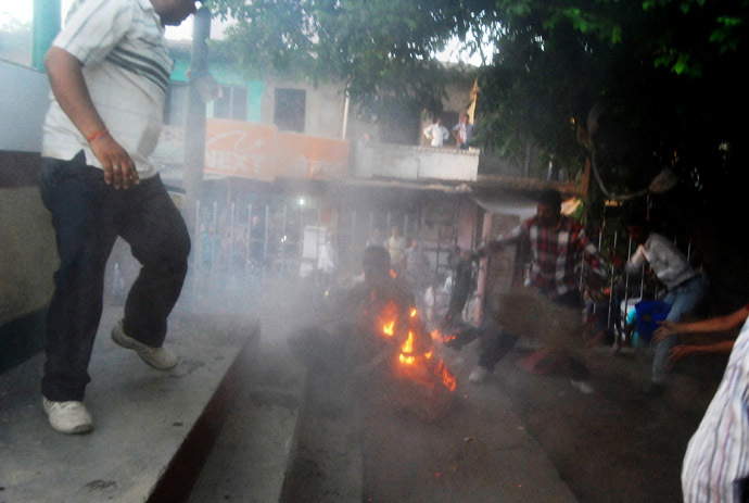 Indian bystanders attempt to douse the blaze during an election television debate in a local park in Sultanpur. (AFP Photo)