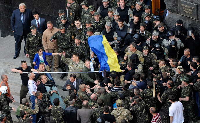 A handout picture released on April 30, 2014 by Ukrainian Prime Minister Press Office shows Maidan self-defence activists fighting with police special team guarding the Ukrainian Cabinet of the Ministers as a man holds an Ukrainian national flag in Kiev on April 30, 2014 (AFP Photo / Andrey Krafchenko)