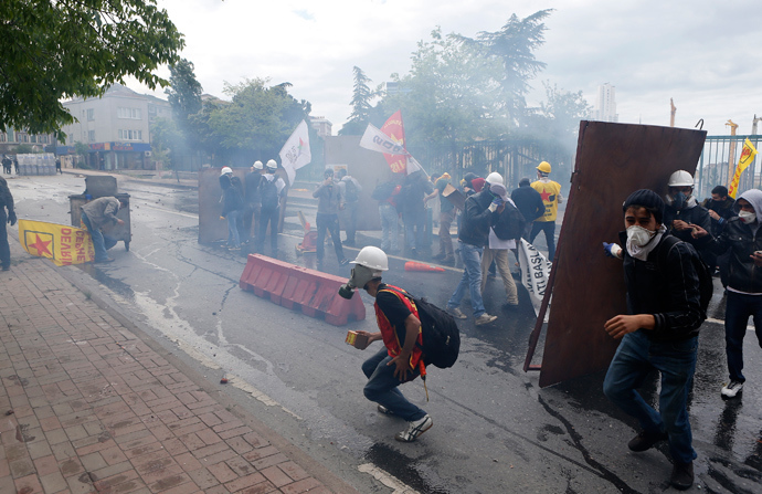 Protesters shield themselves from tear gas fired by riot police during a May Day demonstration in Istanbul May 1, 2014 (Reuters / Umit Bektas)