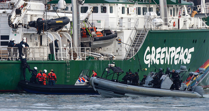 "Dutch police climb onboard the Greenpeace ship, the Rainbow Warrior, after members of Greenpeace draped banners saying ""No Arctic Oil"" from the Russian oil tanker Mikhail Ulyanov, in the harbour of Rotterdam May 1, 2014 (Reuters / Michael Kooren)"