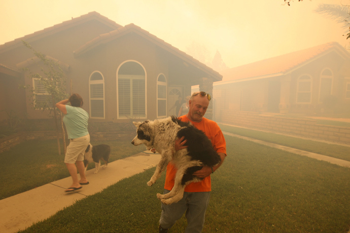 People evacuate from their homes as a wildfire driven by fierce Santa Ana winds closes in on them in Rancho Cucamonga, California, April 30, 2014 (Reuters / David McNew)
