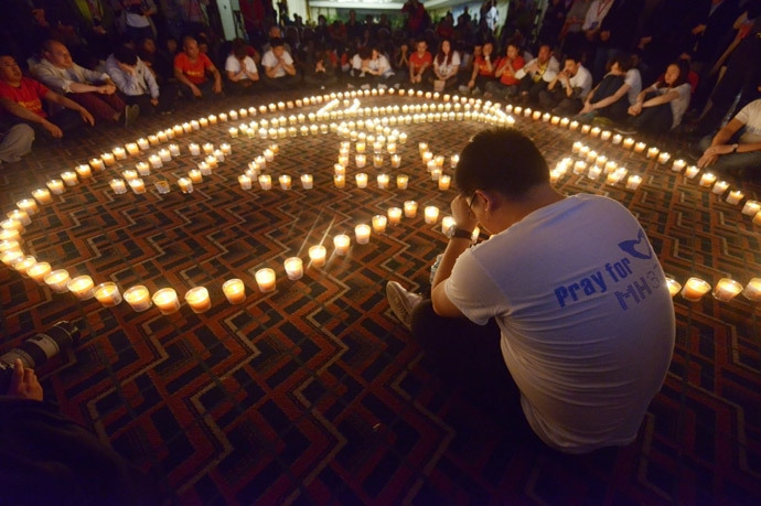 A Chinese relative (R) of passengers on Malaysia Airlines flight MH370 prays in front of candles as he takes part in a prayer service at the Metro Park Hotel in Beijing (AFP Photo / Wang Zhao)